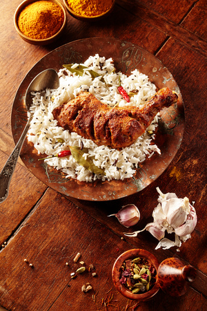 tandoori chicken: Overhead view of Indian styled spicy chicken tandoori and herbed rice in a round plate on a rustic wooden table besides fresh garlic and curry powder