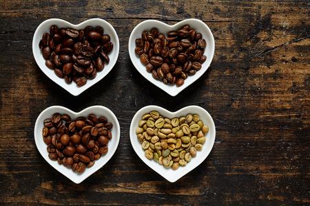 holz: verschiedene Kaffeesorten Roh und ger�stete Bohnen auf rustikalem Holz Hintergrund von oben fotografiert Stock Photo