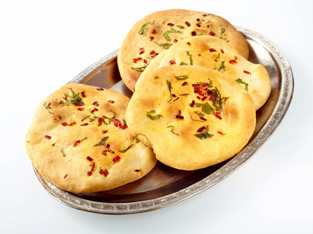 accompaniment: Silver plate full of of four circular naan bread rolls garnished with red and green tasy herbs on white surface Stock Photo