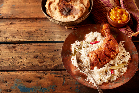 accompaniment: Rustic table set with indian cuisine of spicy chicken and rice with fresh chutney besides toasted flat bread Stock Photo