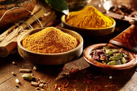 Erfreulicherholztisch mit Boden und vollständiges Currypulver und Kurkuma neben harten Bambus-Sticks in Schalen beleuchtet Standard-Bild - 55746740