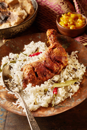 tandoori chicken: Close up of a hearty indian chicken drumsticks tandoori meal with spicy chicken and herbed rice in round dish with silver spoon besides dipping sauce