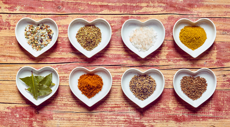 sexual selection: Assorted culinary spices and condiments in heart shaped dishes arranged in two rows on a rustic wood background, overhead view