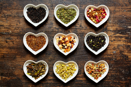 raw tea: Set of nine assorted sorts of raw tea in tiny bowls shaped as hearts on weathered wooden surface