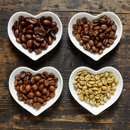 unused: Four light and dark varieties of raw unused coffee beans in separate little heart shaped bowls for java lovers over dark wood background Stock Photo