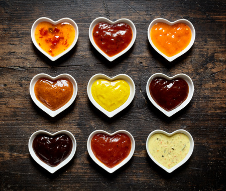 Top down view on nine colorful mild and spicy sauces and marinades filled up inside heart shaped bowls over weathered wooden table
