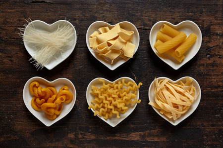 ribbon pasta: Top down from above view on six types of uncooked pasta noodles in neatly aligned heart shaped bowls for italian cuisine lovers over dark wood background