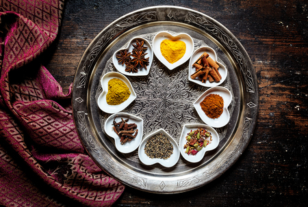 holz: Round silver platter besides silk scarf on table holds eight white heart shaped trays with a variety of colorful spices