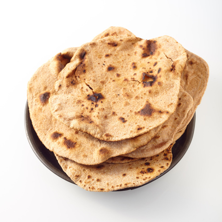 black gram: Close up of indian wheat flour flat chapati bread toasted on top and placed in a round bowl against a white background Stock Photo