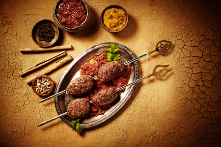 top down: Top down view of shish kebob meat Indian style in pewter plate with sauces and spices with dried bamboo sticks on cracked paint surface Stock Photo