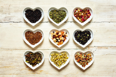 top down: Top down view on nine colorful mild and spicy culinary tea sorts filled up inside cute little heart shaped containers over weathered white wooden table