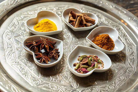 sexual selection: Various culinary asian spices ground or shredded in little piles within white heart shaped dishes over ornate silver platter and wood background
