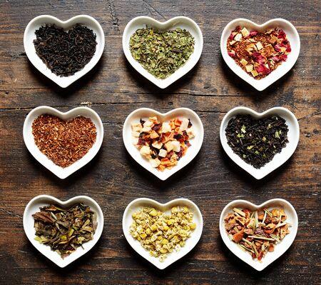 Stil: Herzchen Schalen mit neun unterschiedlichen Teesorten auf Holz Hintergrund in rustikalem Stil