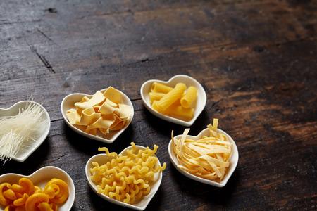 holz: Kleine Herz Schalen gef�llt mit Nudeln, sortiert. Nudelsorten arrangiert auf dunklem braunem Holz Untergrund mit Gestaltungsfreiraum oder Textfreiraum f�r italienische Pasta Konzepte.