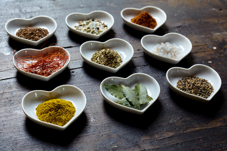 sexual selection: Variety of cooking spices and condiments displayed in heart shaped dishes on an old black wooden table, low angle view