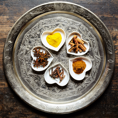 Various spices and culinary herbs ground or shredded in neat piles within white heart shaped dishes over ornate silver platter and wood background