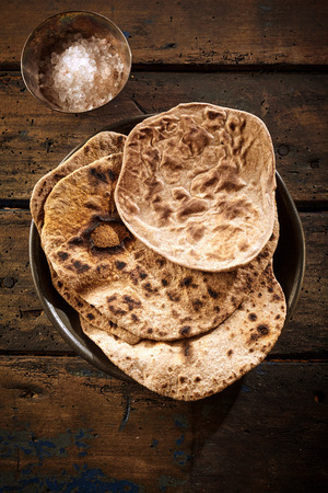 top down: Top down view of hot flat bread in cast iron bowl with cup of flour on weathered wooden background Stock Photo