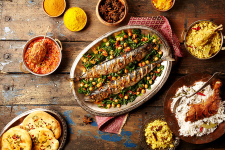 top down: Top down view on baked fish indian style surrounded by rice, bread, sauces and various spices on weathered wooden surface