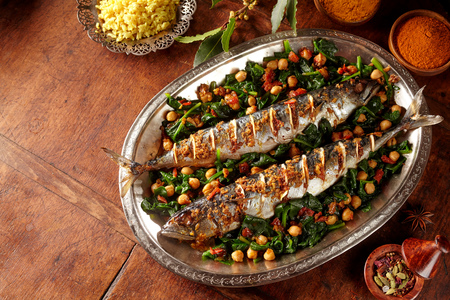 copyspace: Spicy cooked mackerel fish stuffed with spices and garnished with vegetables and garbanzo beans in large silver platter over table with copy space