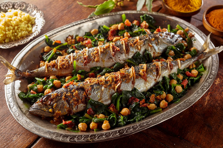 recipes: Spicy cooked mackerel fish stuffed with spices and garnished with vegetables and garbanzo beans in large silver platter