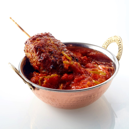meat food: Elegant metal handled round bowl of hot sauce with meat kebab inside over white reflective background