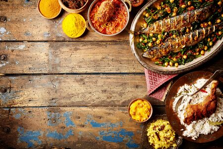 copyspace: Top down view on baked fish indian style surrounded by rice, bread, sauces and various spices on weathered wooden surface with copy space