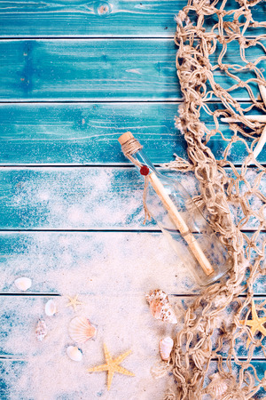 Nautical themed backdrop with message in a bottle, starfish and a fishing net arranged as a side border on turquoise blue wooden boards with copy space
