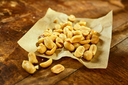 Heap of healthy fresh roasted and salted peanuts on crumpled paper on a wooden table for a nutritious snack, close up view