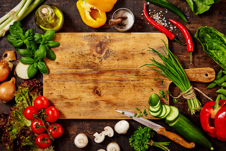 chopping: High Angle Still Life View of Knife and Wooden Cutting Board Surrounded by Fresh Herbs and Assortment of Raw Vegetables on Rustic Wood Table