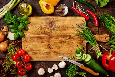 High Angle Stilleben Blick auf Messer und Holz Schneidebrett umgeben von frischen Kräutern und Sortiment von rohem Gemüse auf rustikalen Holz Tisch Standard-Bild