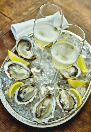 charolas: Close up on oysters set up around silver platter filled with crushed ice, lemon slices and champagne glasses in middle