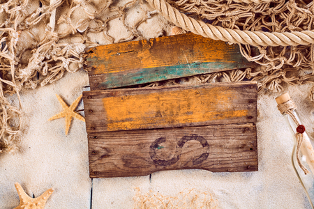 waif: Blank rustic wooden sign with a nautical theme surrounded by a fishing net, starfish and message in a bottle with scattered sand on wooden boards Stock Photo