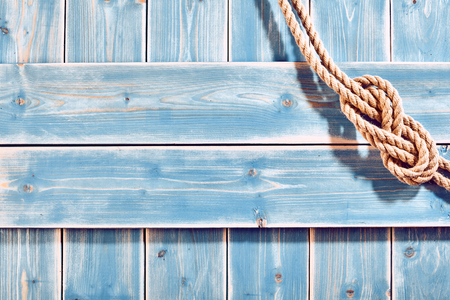 tied down: Nautical Themed Background - High Angle Still Life of Double Figure Eight Knot in Natural Rope Across Corner of Blue Painted Wood Plank Background with Copy Space Stock Photo