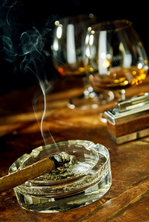 tilted view: Tilted angle view of cigar sitting in glass ashtray by fancy lighter and two goblets filled with bourbon Stock Photo