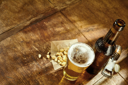bottle cap opener: High Angle Still Life View of Glass of Cold Ale, Bottle of Beer, Bowl of Peanuts and Bottle Cap Opener on Rustic Wooden Table with Copy Space Stock Photo