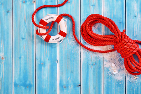 buoyancy: Red colored thick rope with loose knot around ringed white life preserver over blue wood paneling with sand, seashells and copy space