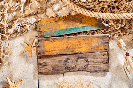 waif: Single old wooden blank sign with rusty nails and faded paint over sand, message in a glass bottle, starfish, seashells and fishing net for name or other text