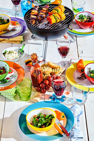 Well Laid summer table with colorful dish and plates and brazier on white background with vegan bbq skewers Stock Photo