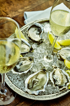 shucked: Close up on oysters arranged around inside of silver platter filled with crushed ice and champagne glasses