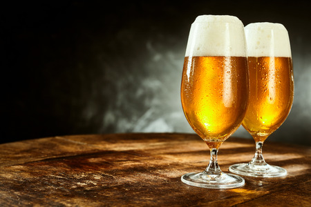 Two glasses full of beer on weathered wooden table with black and gray background