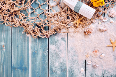 themed: Marine or nautical themed background with a fishing net, starfish and message tied and rolled on scattered beach sand, starfish and shells, copy space below Stock Photo