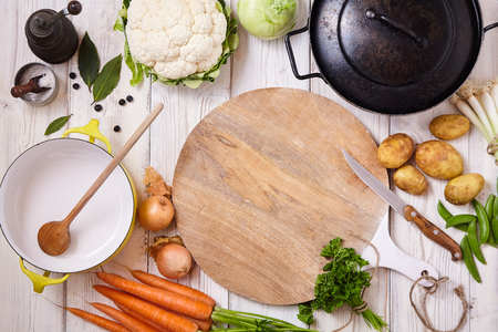 high angle: High Angle Still Life View of Cutting Board, Knife and Wok Frying Pan Surrounded by Fresh Raw Vegetables on Painted Wood Table - Preparing a Meal with Raw Ingredients