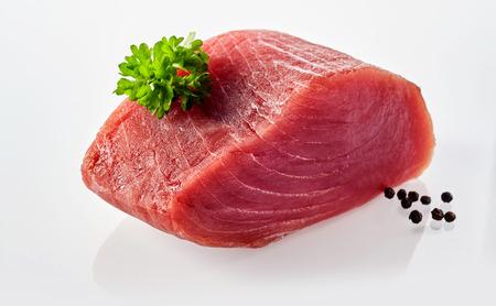 Todavía vida de la losa de pescado de atún sin procesar en el fondo blanco adornado con negro pimienta y ramillete de hierbas frescas verdes