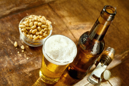 bar top: High Angle Still Life View of Glass of Cold Ale on Rustic Wooden Table Beside Bottle of Beer, Bowl of Peanuts and Bottle Cap Opener