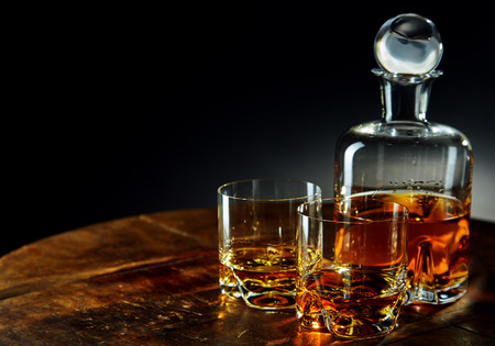 Decanter of whiskey besides two glasses half filled on a round wooden table in a dark room