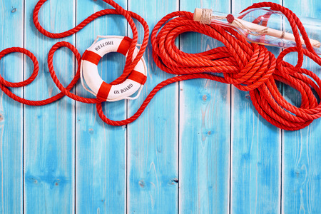 Partially unraveled red rescue rope and ring shaped life preserver beside message in a glass bottle over weathered blue wood paneled background