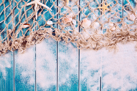 waif: Weathered wooden blue plank background with sand, rope fishing net starfish and seashells with copy space Stock Photo