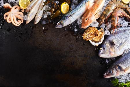 Elevada Naturaleza muerta Vista de la variedad de pescado crudo y mariscos que se enfría en hielo con limón y dispuestas alrededor de la frontera de la imagen en rústica superficie de la mesa de madera con espacio de copia