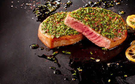 dirtied: Close Up Still Life of Seared Tuna Steaks Topped with Fresh Herb Pesto Crust on Dark Gray Surface Dirtied with Oil and Lemon Slices