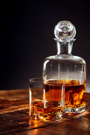 bourbon: Glass of whisky besides decanter on a round wooden table against a black background Stock Photo
